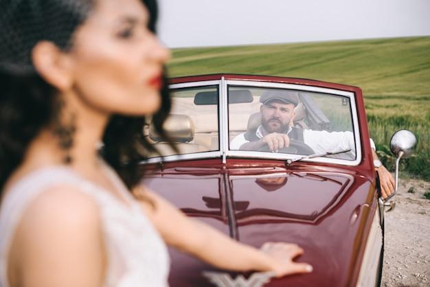 Стильная свадебная пара возле ретро автомобиля