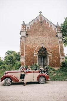 Стильная свадебная пара возле церкви в ретро-автомобиле.