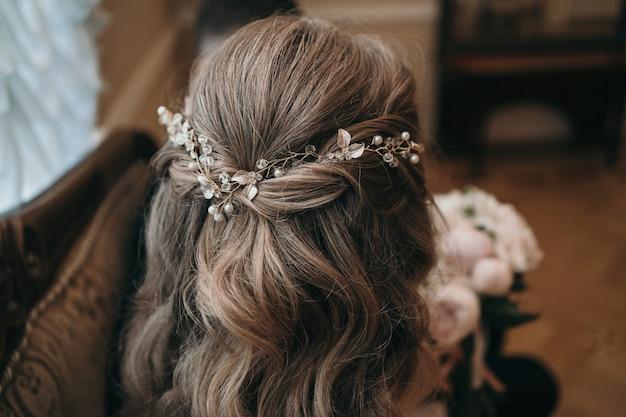 花嫁の髪型のスタイリッシュな結婚式の髪の装飾美しいウェーブのかかった髪のクローズアップ