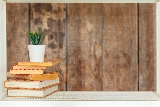 Stylish white bookshelf against grunge wooden wall