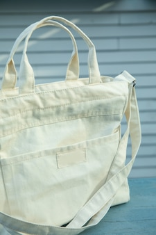 Stylish white eco bag outdoor on wooden surface