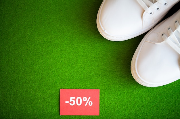 Stylish white fashion sneakers on gren .