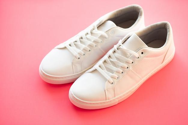 Stylish white fashion sneakers on pink .