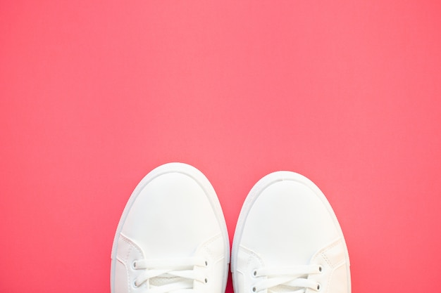 Stylish white fashion sneakers on pink .
