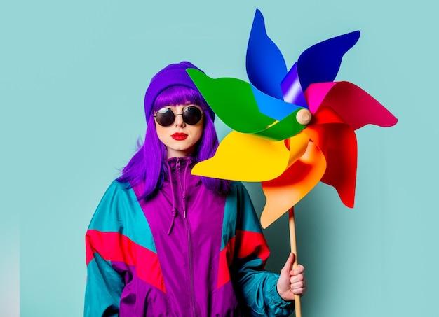 紫色の髪とトラックスーツを持つスタイリッシュな白い女の子は青い壁に風車を保持します
