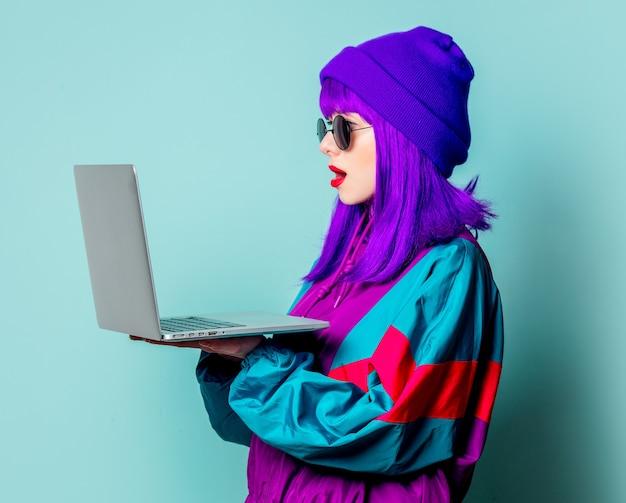 Стильная белая девушка с фиолетовыми волосами и спортивным костюмом с ноутбуком на синей стене