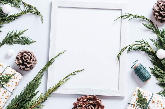 Stylish white and green christmas flat lay with huge pine cones, cedar branches, presents and decorations