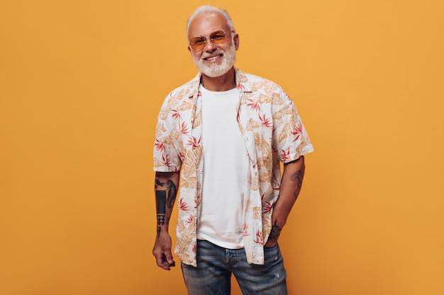 흰색 티셔츠, 청바지, 선글라스를 입은 세련된 흰색 머리 남자가 외진 벽에 포즈를 취하고 있다