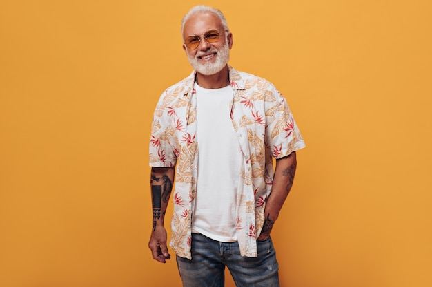 Stylish white haired man in white t-shirt, jeans and sunglasses poses on isolated wall
