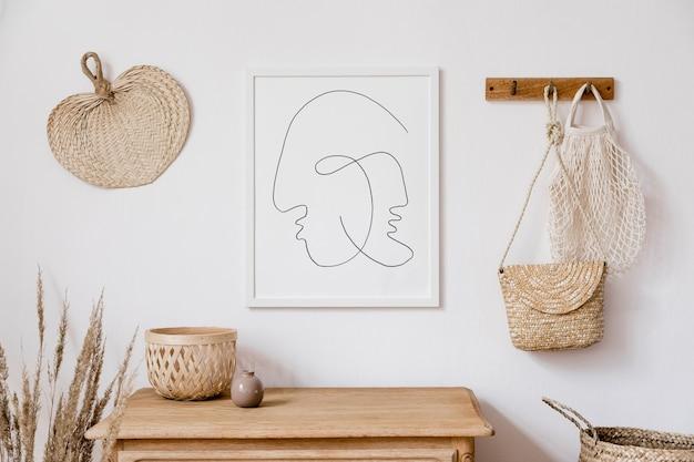 モックアップポスターフレーム、籐の装飾、葉、木製の棚、ドライフラワー、エレガントな個人的なものを備えたリビングルームのスタイリッシュな白いインテリア。家の装飾の中立的な概念。テンプレート。
