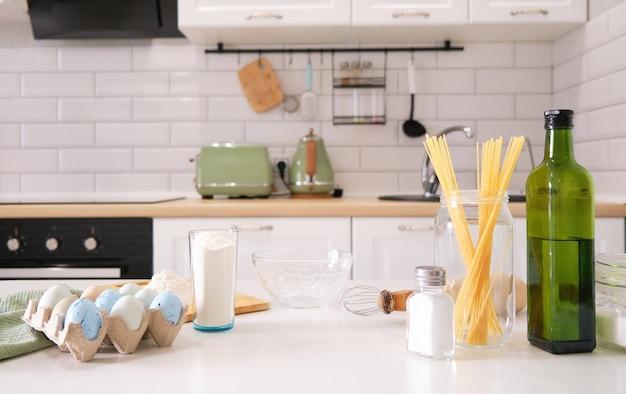 Стильный белый кухонный фон с кухонной утварью и зеленым комнатным растением, стоящим на белой столешнице, копией пространства для текста, вид спереди