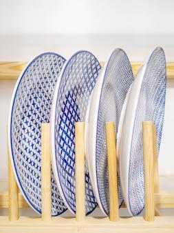 青い模様のスタイリッシュな白いプレートが木製のスタンドに立つ。キッチンインテリアデザインのコンセプト。縦の写真。