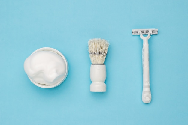 Stylish white shaving accessories on a light blue background.