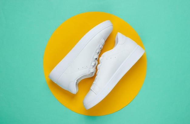 Stylish white sneakers on blue paper with yellow circle