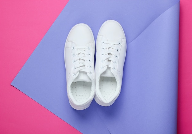 Stylish white sneakers on folded paper