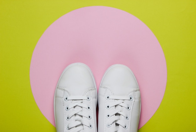 Stylish white sneakers on green paper with pink pastel circle