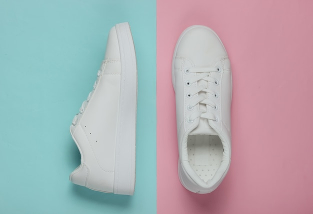 Stylish white sneakers on pink blue pastel paper