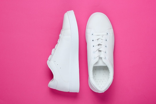 Stylish white sneakers on pink paper with pink circle