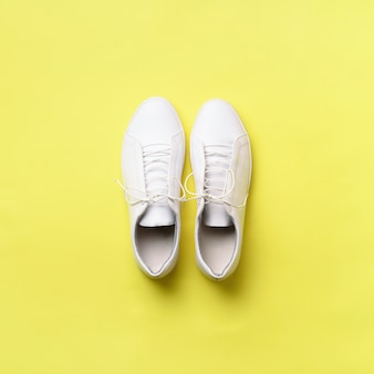 Stylish white sneakers and rope on yellow background with copy space.