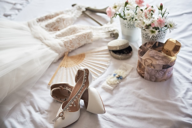 Stylish white wedding bridal shoes, dress, perfume, flowers and jewelry on white