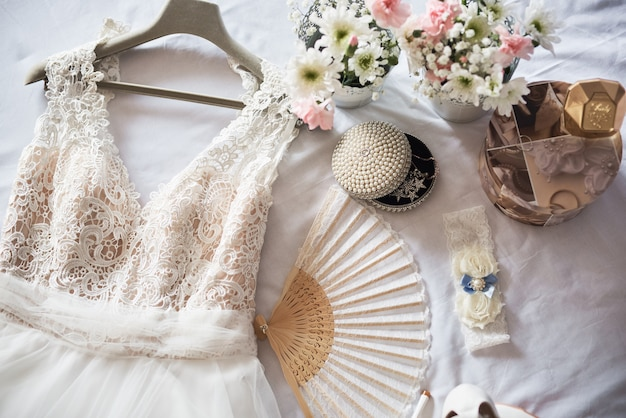 Stylish white wedding bridal shoes, dress, perfume, flowers and jewelry.
