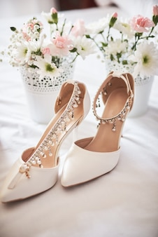 Stylish white wedding bridal shoes, perfume, flowers and jewelry.