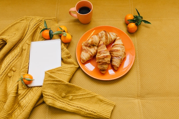 Stylish winter image in orange colors from above of knitted sweater, croissants, clementines and notebook on table