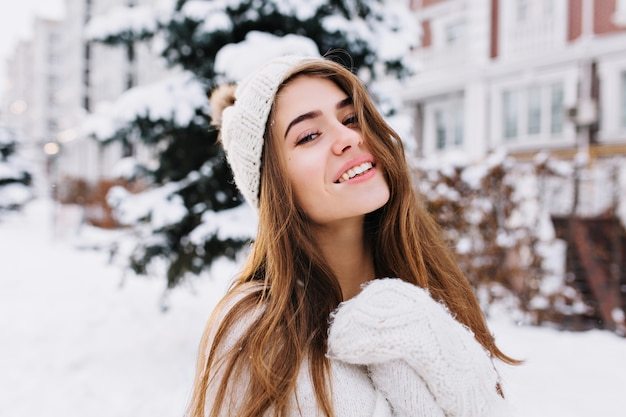 Stylish winter portrait of charming young woman with long brunette hair, in woollen white gloves and hat walking on street full with snow. cheerful mood, smiling.