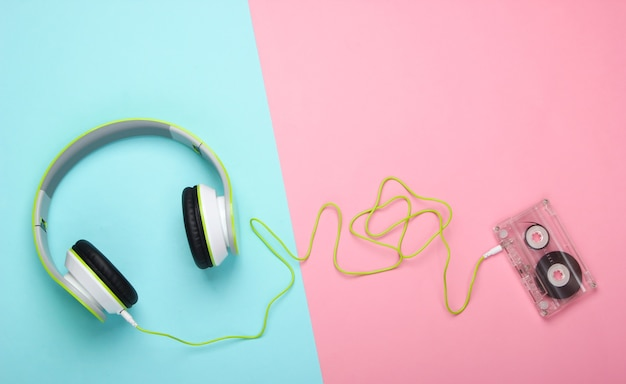 Stylish wired stereo headphones with audio cassette on pink blue pastel surface
