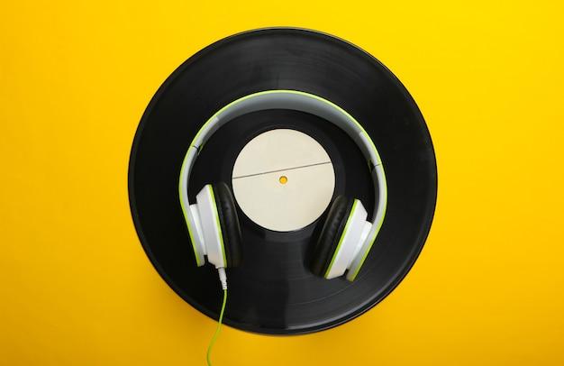 노란색 표면에 비닐 레코드가있는 세련된 유선 스테레오 헤드폰