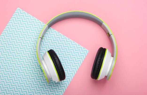 Stylish wireless stereo headphones on pink blue pastel surface