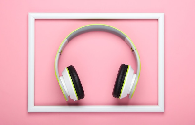 Stylish wireless stereo headphones on pink pastel surface with white frame