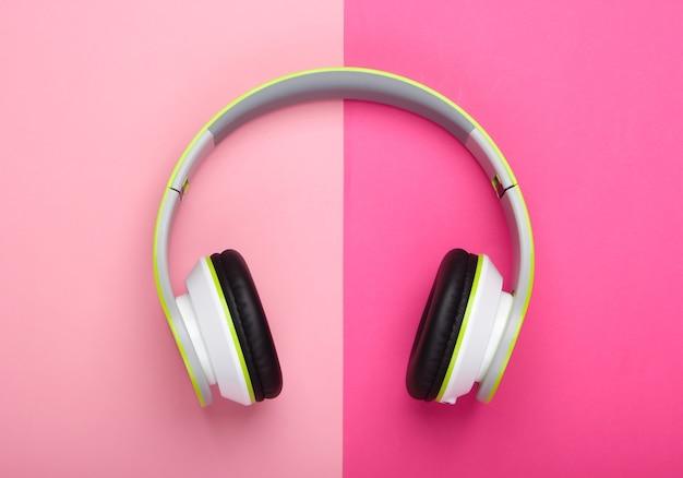 Stylish wireless stereo headphones on pink pastel surface