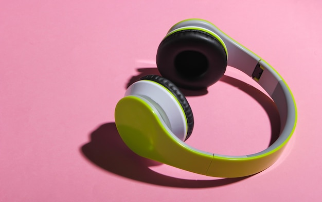 Stylish wireless stereo headphones with shadow on pink pastel surface
