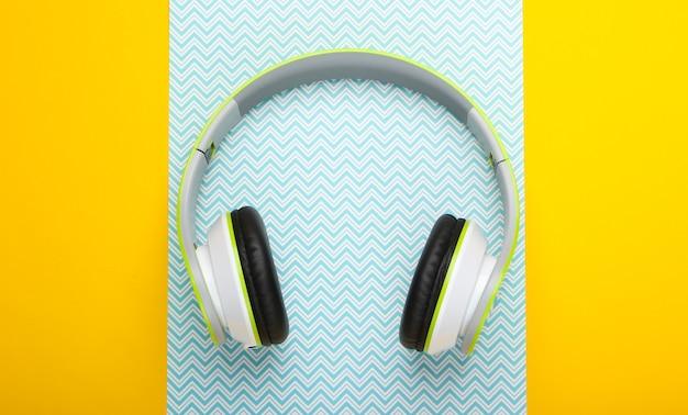 Stylish wireless stereo headphones on yellow blue pastel surface