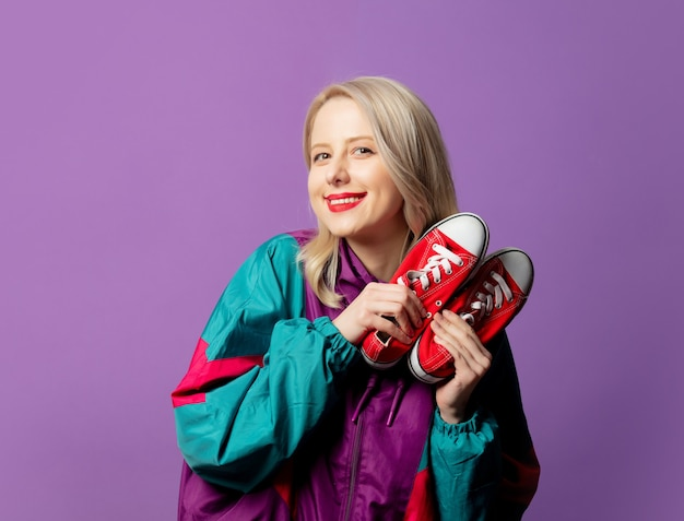 Stylish woman in 80s windbreaker and roud sunglasses holds red gumshoes on purple wall