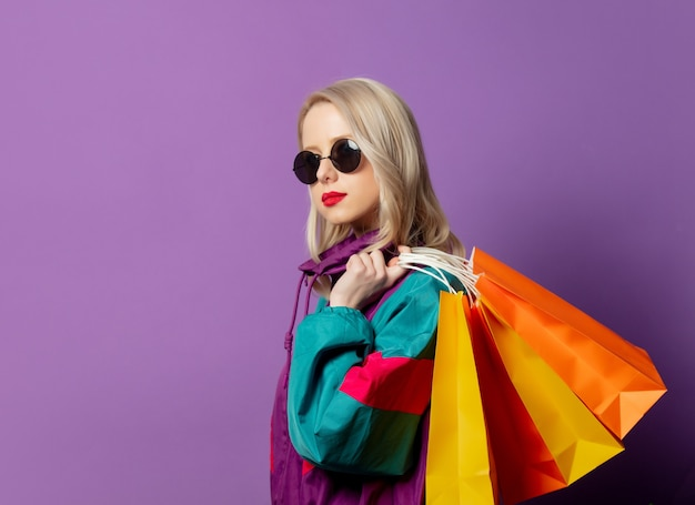 Stylish woman in 80s windbreaker and roud sunglasses holds shopping bags on purple wall