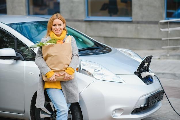 ショッピングバッグで商品を購入した後のスタイリッシュな女性が充電中の電気自動車の近くに立っています