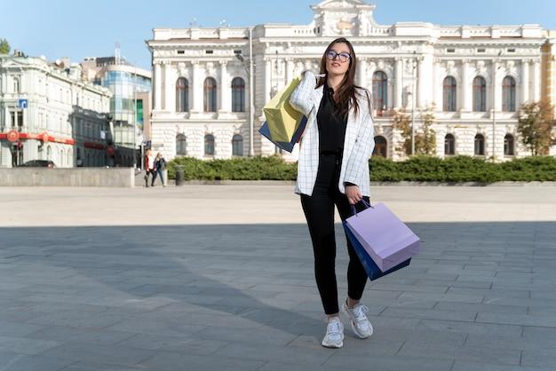 도심에서 화려한 가방과 함께 쇼핑 후 세련 된 여자. 좋은 쇼핑 하루.