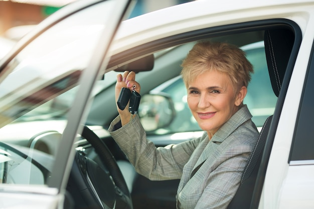 Stylish woman in age, in a suit sits behind the wheel of a car in the summer with keys