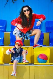 Стильная женщина и маленький мальчик позирует на баскетбольной площадке.