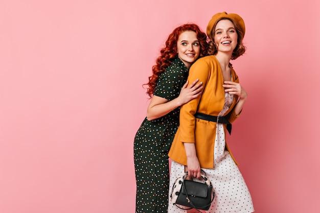 Donna alla moda in berretto che abbraccia con un amico. due ragazze eleganti che posano insieme su sfondo rosa.