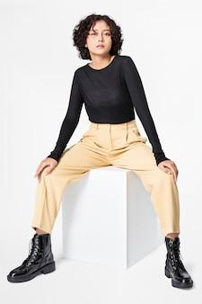 Donna alla moda in maglietta nera a maniche lunghe e pantaloni beige abbigliamento casual moda corpo intero