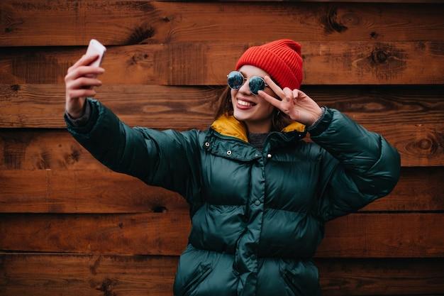 Blogger donna elegante in abito multicolore brillante fa selfie sulla parete di legno