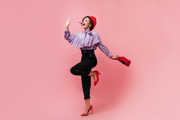 Stylish woman in blouse with flounces and red beret holds bag and waves hand with smile.