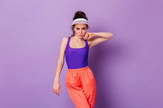 Stylish woman in cap and outfits from 80s posing on purple wall