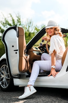 Stylish woman in car full shot