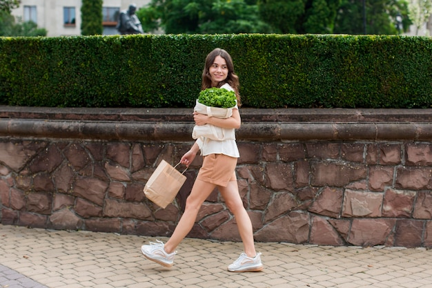 Stylish woman carrying groceries bag
