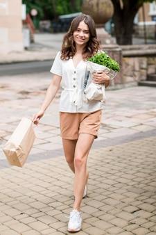 Стильная женщина, несущая сумку для продуктов