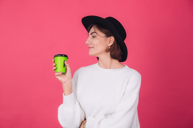 Stylish woman in casual white sweater and hat on pink red wall